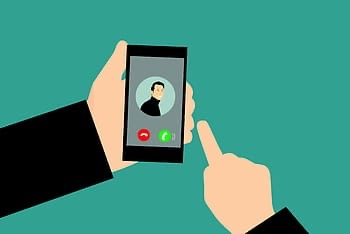 Image of person holding cell phone with screen showing a video call.
