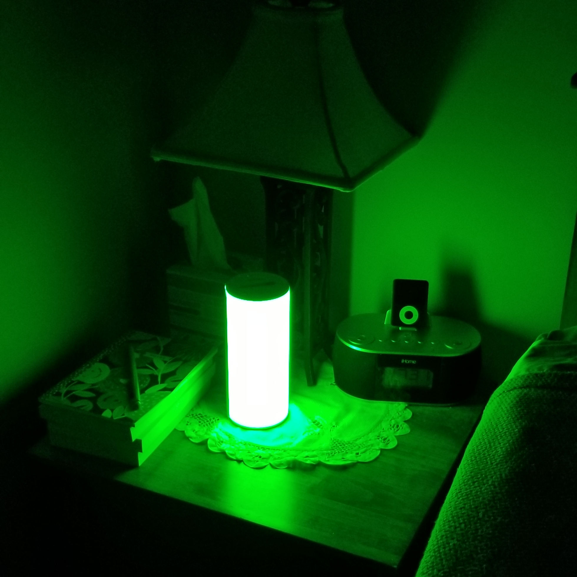 Allay Lamp lit white on bedside table with traditional lamp, books, and a clock radio.